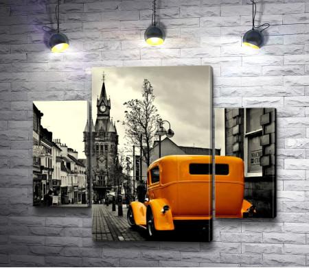 Оранжевый автомобиль в черно белом городе