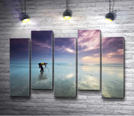 Парень фотографирует невероятный закат над морем
