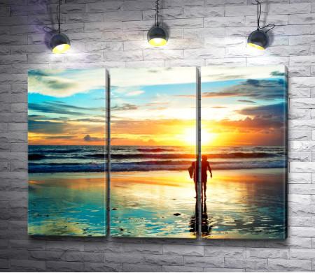 Прогулка серфера по пляжу в свете заката