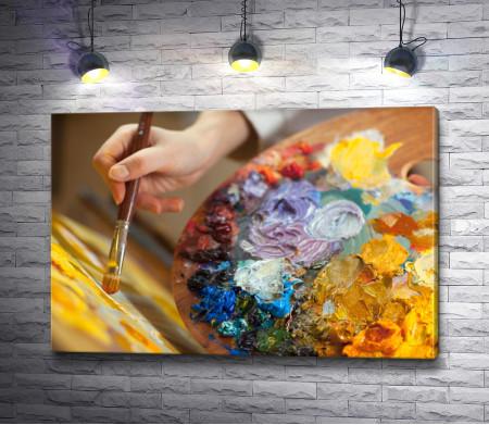 Рука художника с палитрой красок