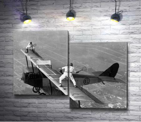 Игра в теннис на крыльях самолета. Черно-белое фото
