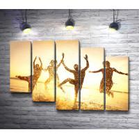 Люди танцуют на берегу моря во время заката