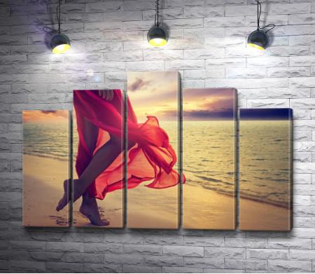 Ноги девушки в шелковой красной юбке на пляже