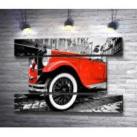Красный ретро-автомобиль в черно-белом городе