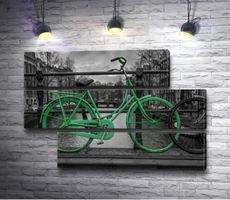 Зеленый велосипед на мосту на фоне черно-белого города
