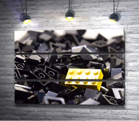 Желтый конструктор на куче черного