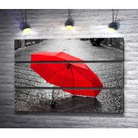 Красный зонт лежит на асфальте