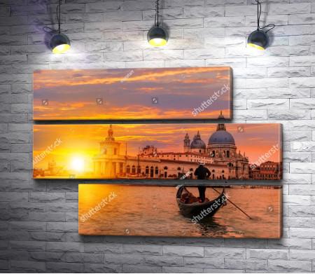 Гондольер плывет по каналу Венеции