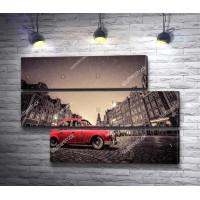Красный ретро автомобиль на булыжной мостовой