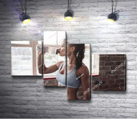 Девушка со спортивной фигурой пьет воду в фитнес зале