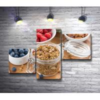 Баночка с мюслями, блюдца со свежими ягодами и орехами