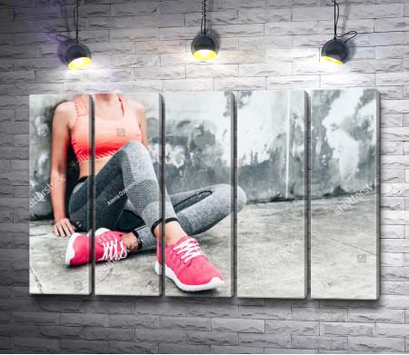Спортивная девушка сидит у стены