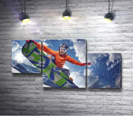 Парень сноубордист выполняет трюк