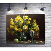 Желтый букет из веточек мимозы и нарциссов в вазе с бокалом вина и старинными часами