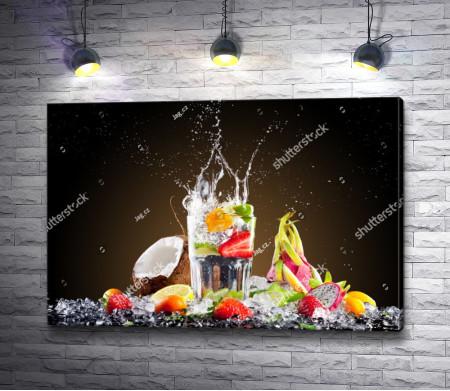 Тропический коктейль с кубиками льда и ягодами с фруктами