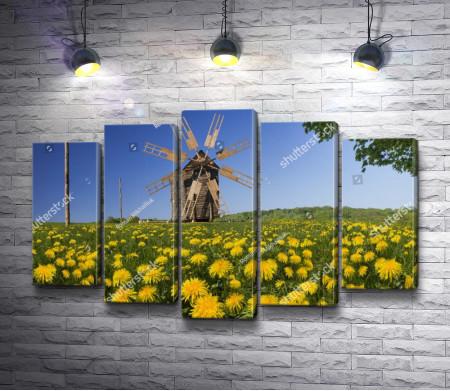 Деревянная мельница на лугу с желтыми одуванчиками