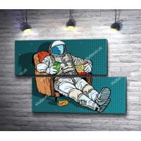 Астронавт сидит в кресле с едой