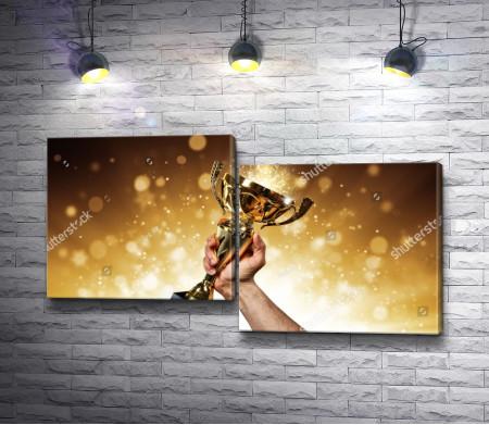Мужчина держит в руке золотой кубок-трофей