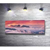 Пик горы, возвышающийся над облаками, во время заката