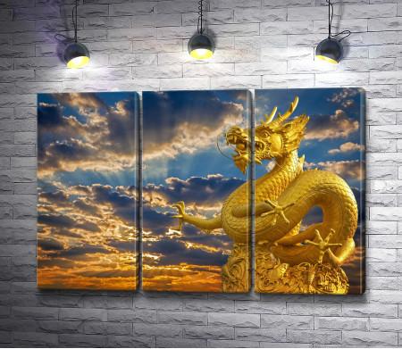 Статуя золотого дракона на фоне заката