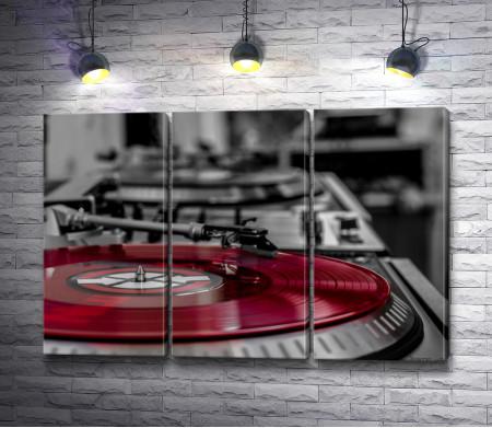 Красная виниловая пластинка в проигрывателе, черно-белое фото с акцентом