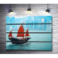 Корабль с красными парусами на фоне города