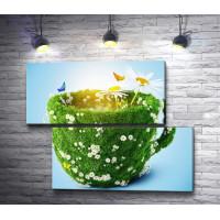 Чашка в траве с ромашками