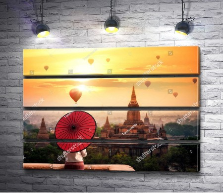 Девушка с красным зонтом смотрит на город в лучах заката