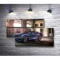 Синий BMW 8 Series на пустой парковке в лучах солнца