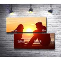 Парень и девушка беседуют на фоне заката