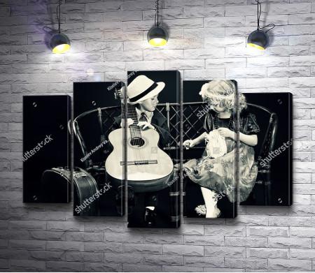 Мальчик играет на гитаре для очаровательной девочки