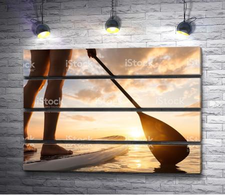На доске с веслом