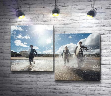 Серфингисты бегут по берегу