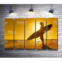 Девушка серфингиста на фоне заката