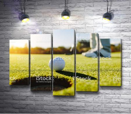 Мячик для гольфа перед лункой