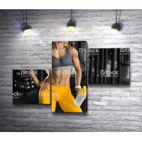 Девушка в желтых лосинах в фитнес зале